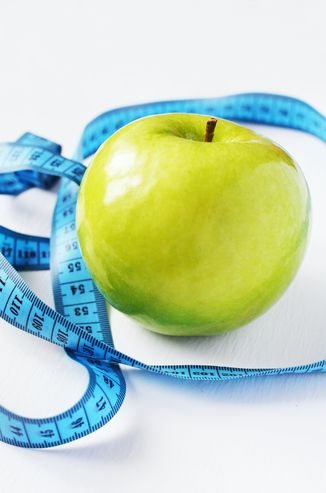 A healthy apple and measuring tape