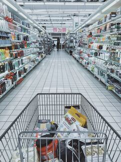 A shopping trolley down the aisle of a supermarket