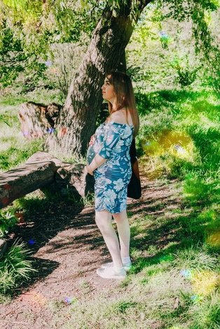 A pregnant women standing in a forrest
